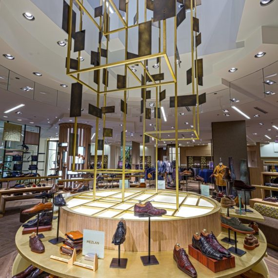 The Sculpture lands on a 10' diameter shoe fixture fabricated from cerused white oak and cantilevered, radiating brass shelves.