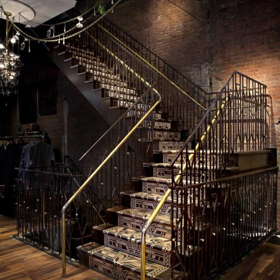 Fabricated from laser-cut steel and machined brass components, the three-story tall staircase was fabricated and finished with a blackened and rusted patina.